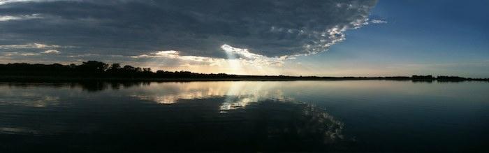beams of light thru cloud near sunset over lake